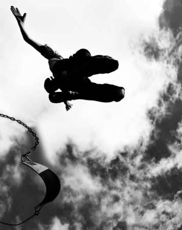 man-jumping-off-swing