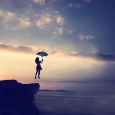 girl-jumping-off-cliff-with-umbrella