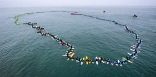 "A total of 511 surfers float on their boards and hold hands in the ocean to create the world's largest paddle out ""Circle of Honor"" in Huntington Beach Tuesday morning, June 20, 2017. (Photo by Mark Rightmire, Orange County Register/SCNG)"