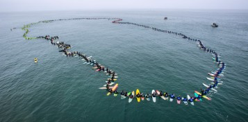 """A total of 511 surfers float on their boards and hold hands in the ocean to create the world's largest paddle out """"Circle of Honor"""" in Huntington Beach Tuesday morning, June 20, 2017. (Photo by Mark Rightmire, Orange County Register/SCNG)"""