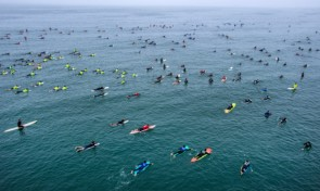 """Hundreds of surfers paddle into place just north of the Huntington Beach Pier in Huntington Beach as they create the world's largest paddle out """"Surfing Circle of Honor"""" in Huntington Beach Tuesday morning, June 20, 2017. (Photo by Mark Rightmire, Orange County Register/SCNG)"""