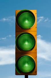All green traffic light with a blue sky.